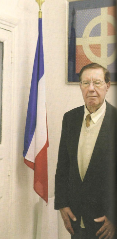 Pierre Sidos à côté du drapeau français et devant l'embême de l'OEuvre française