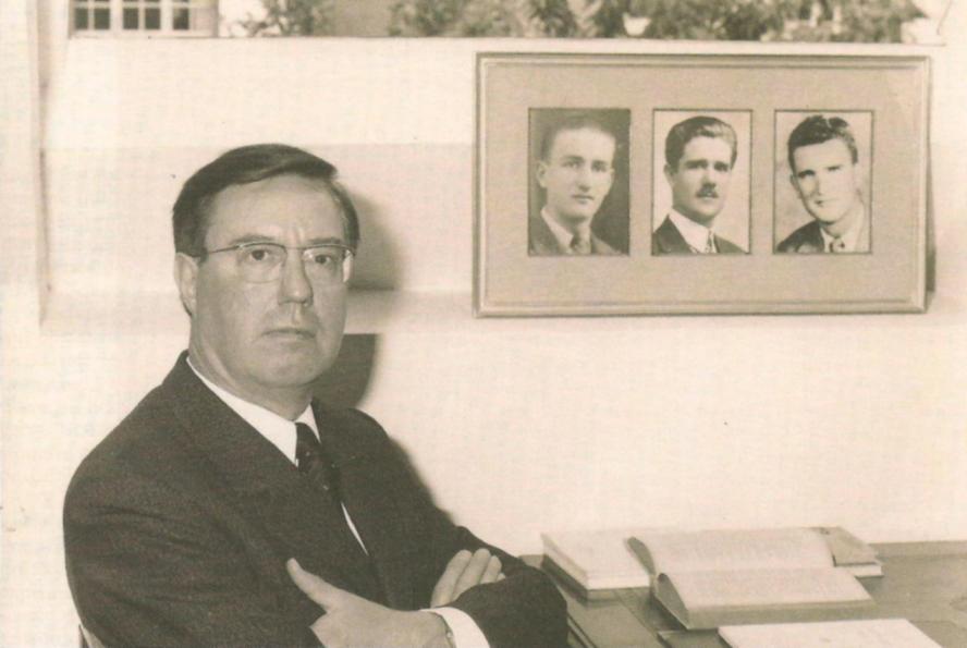 Pierre Sidos devant son bureau. Sur la photo au mur au centre son père François, et ses deux frères, Jean (à gauche) et Henri (à droite)
