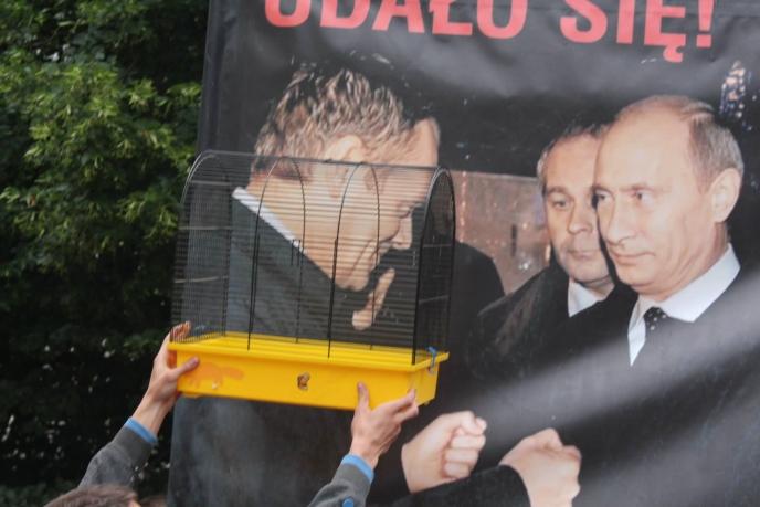 [Un manifestant présente une cage devant la photo de Donald Tusk, ici avec Vladimir Poutine]